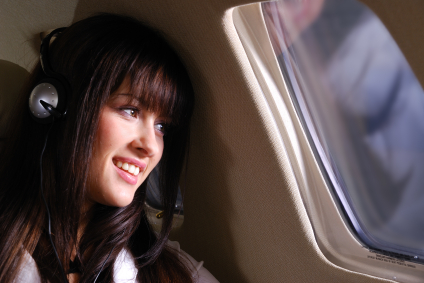 Young business woman listen music and enjoying the flight in the small private airplane.